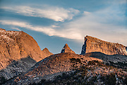 """East Temple Peak at sunset, in Bridger Wilderness, Wind River Range, Bridger-Teton National Forest, Rocky Mountains, Wyoming, USA. Backpack to Big Sandy Lake Campground (11 miles round trip with 1000 feet gain). Day hike from Big Sandy Lake to Clear Lake and Deep Lake below East Temple Peak then loop back via Temple Lake, Miller Lake, and Rapid Lake (7.5 miles, 1060 ft gain) on the Continental Divide Trail. Wind River Range, Bridger-Teton National Forest, Rocky Mountains, Wyoming, USA. The Continental Divide follows the crest of the """"Winds"""". Mostly composed of granite batholiths formed deep within the earth over 1 billion years ago, the Wind River Range is one of the oldest mountain ranges in North America. These granite monoliths were uplifted, exposed by erosion, then carved by glaciers 500,000 years ago to form cirques and U-shaped valleys."""