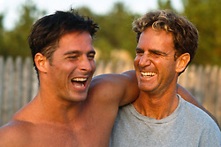 Two men laughing while leaning on one another