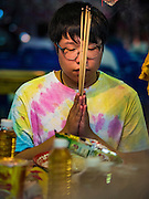 15 OCTOBER 2015 - BANGKOK, THAILAND:  A person prays during the Vegetarian Festival at the Joe Sue Kung Shrine in the Talat Noi neighborhood of Bangkok. The Vegetarian Festival is celebrated throughout Thailand. It is the Thai version of the The Nine Emperor Gods Festival, a nine-day Taoist celebration beginning on the eve of 9th lunar month of the Chinese calendar. During a period of nine days, those who are participating in the festival dress all in white and abstain from eating meat, poultry, seafood, and dairy products. Vendors and proprietors of restaurants indicate that vegetarian food is for sale by putting a yellow flag out with Thai characters for meatless written on it in red.   PHOTO BY JACK KURTZ