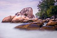 Orange lichen covered granite rocks in the surf on Batu Ferringhi beach in Penang.