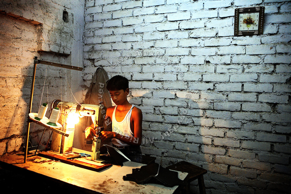 A child is sewing parts of what will be leather articles, inside a medium-size manufacturing unit in Jajmau Industrial Area, Kanpur, Uttar Pradesh.