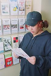 Female client reading leaflet about resettlement hostels,