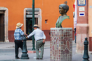 Men wearing Panama hats chat along the Plaza Principal in Dolores Hidalgo, Guanajuato, Mexico. Miguel Hildago was a parish priest who issued the now world famous Grito - a call to arms for Mexican independence from Spain.