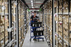 A worker picks and scans clothing from thousands of clothing racks at Amazon's fulfillment centre in Swansea, in the run up to Black Friday.