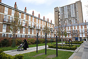 A lady, wearing a niqab and pushing a pram, walks while looking at her mobile phone on 27th April 2016 near Balfron Tower in East London, United Kingdom. Balfron Tower in Poplar was designed by the celebrated architect Ernő Goldfinger and opened in 1967. From the series Our Small World an observation of our mobile phone obsessions.