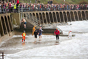 Crowds gather for Folkestone Lions Club Boxing Day Dip.  An annual fancy dress fundraising event, where all sorts of amusing costumes and characters enter the cold sea of the English Channel at Sunny Sands, Folkestone. UK.