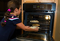 """Faith puts her apple pie in the oven with the others at Gilford Library during their after school """"pie making"""" activity on Tuesday.  (Karen Bobotas/for the Laconia Daily Sun)"""