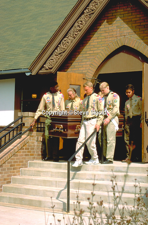 Eagle scout pallbearers carrying coffin of adult leader after funeral.  St Paul  Minnesota USA