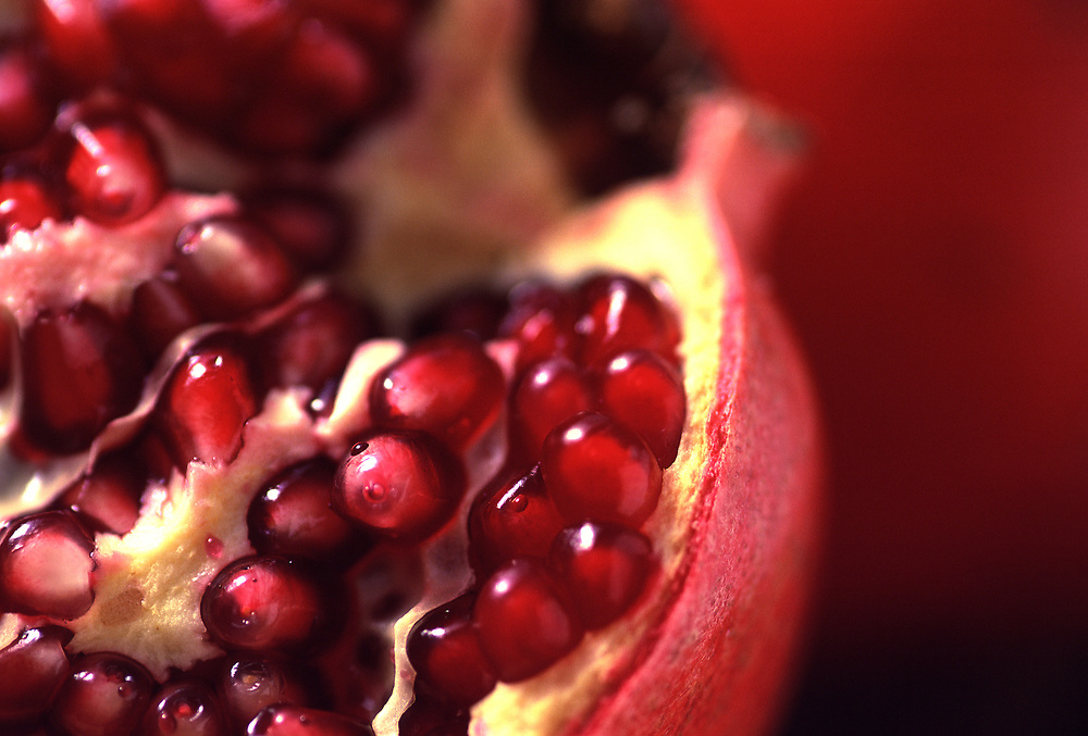 Extreme close up selective focus photograph of a couple of Pomegranates with one broken open to expose the beads of fruit