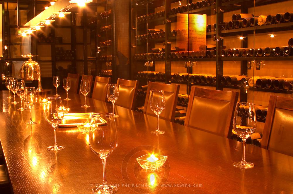 A wine tasting room with glasses on the table and lit candles. Wine racks with old wine bottles in the background. Golden light. Ulriksdal Ulriksdals Wärdshus Värdshus Wardshus Vardshus Restaurant, Stockholm, Sweden, Sverige, Europe