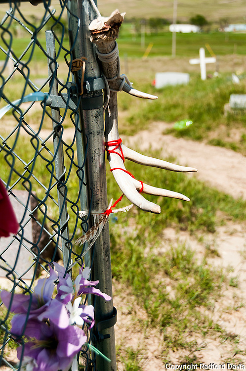 The cemetery at Wounded Knee, where those killed in the winter of 1890 where buried in a pit. Mementos and tokens of remembrance hang on the fence and adorn graves.