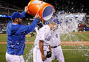 Kansas City Royals pitcher Jeremy Guthrie, center, is dunked with water by George Kottaras, left, and Mike Moustakas, right, at the end of a baseball game against the Chicago White Sox at Kauffman Stadium in Kansas City, Mo., Saturday, May 4, 2013. Guthrie pitched a four-hit shutout, beating the White Sox, 2-0.  (AP Photo/Colin E. Braley).