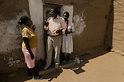 Tchikuteny at the door of his second house at the village, giving orientations to one of his spouses. In Angola?s Namibe desert, at Giraul, in the Namibe province, Tchikuteny, from the Mucubal tribe, is the leader of a big family, maybe the biggest family in the world.<br /> He is the chief leader, the manager and responsible for the entire village. <br /> In his village, Tchikuteny lives nowadays with most of his big family, his 33 wives, that were once 43, but 10 left the village, and most of their descendants.<br /> Tchikuteny maintains the registry of all the new-borns, totalizing 154 sons, and his grandsons, that are around 60. Nowadays, 4 new babies are on the way, and 3 great grand children were born recently.<br /> Huge harmony, love and respect transpire in the village atmosphere. The sense of a community is the pillar of their sustainability and sustenance and their autonomy depends prominently on cattle and agriculture that is made by the villagers. Nevertheless, Tchikuteny village is in close connection with their surrounding communities. Children attend Giraul School and there is proximity and relations with the extended family that lives in the surroundings.<br /> Being the spiritual leader of the community, Tchikuteny is also responsible for the weekly religious works that happens in the village church. <br /> This big family opened his doors to share with us their daily lives.