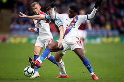 Burnley's Chris Wood and Crystal Palace's Jeffrey Schlupp (right) battle for the ball during the Premier League match at Turf Moor, Burnley.