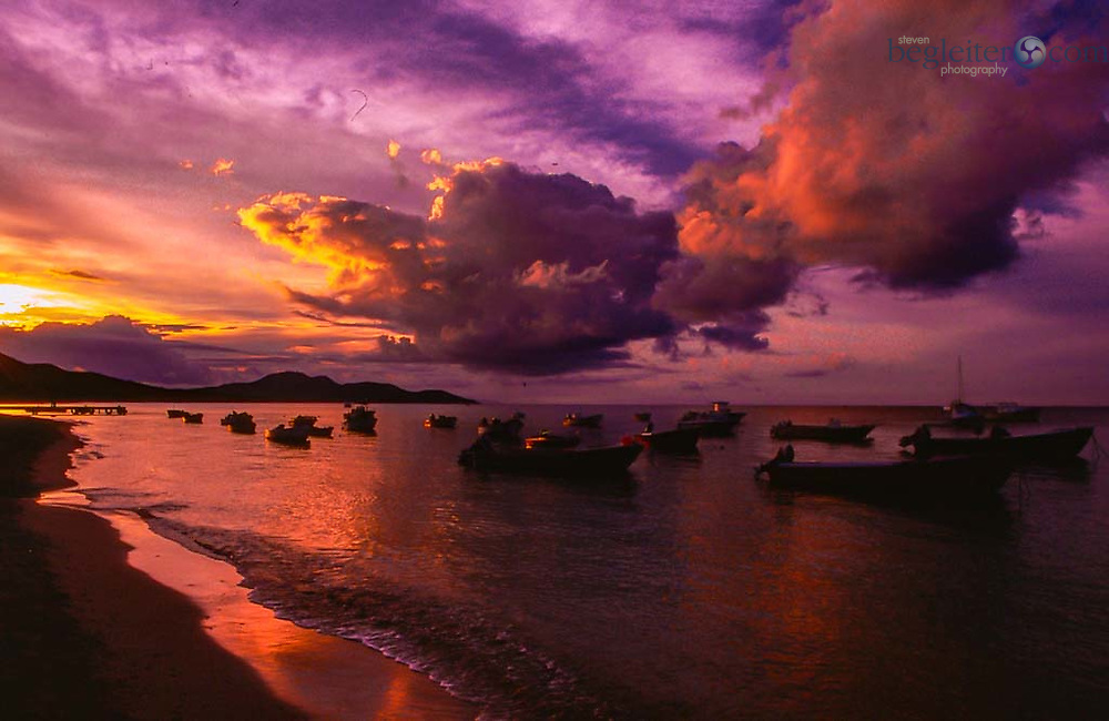 Boats docked in the ocean at sunset