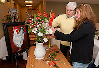 Prior to the opening of Opechee Garden Club's Art 'n Bloom at Gilford Library Maureen Bieniarz-Pond and Carmel Lancia put the finishing touch on Bieniarz-Pond's floral creation interpreted from her artwork Rooster.  (Karen Bobotas/for the Laconia Daily Sun)