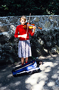 Pretty young girl busking playing violin performing outside Yalta, Crimes, Russia in 1997