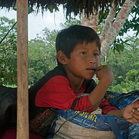 A boy relaxes in his family's hut in San Juan de Yanayacu village in Peru's Amazon Jungle.