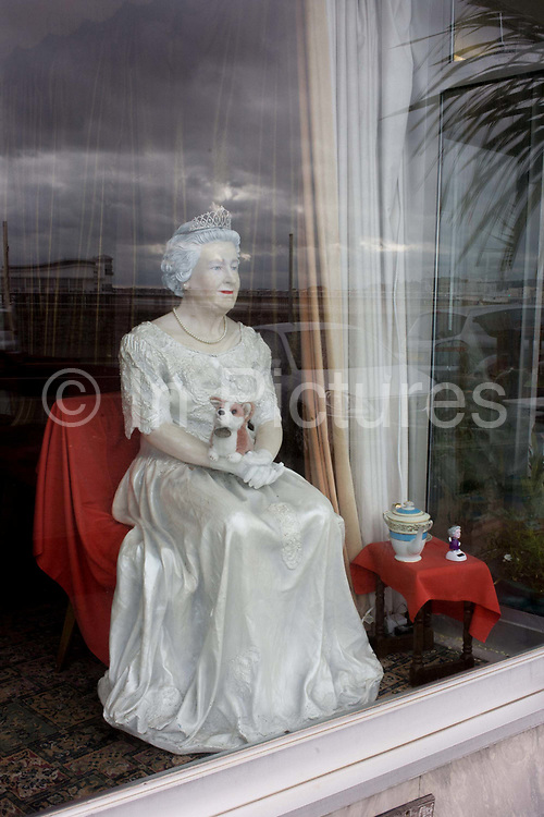 A mannequin of Queen Elizabeth appears in a hotel window on the seafront of Weston-super-Mare, north Somerset. Seated on a throne and holding one of her beloved Corgi pet dogs, the monarch has been placed in the front window of the Midland Hotel on the seafront of this seaside town in England's south-west. She looks cheap and nasty, a not-so welcoming effigy for arriving guests but typical perhaps, of some UK holiday towns still desperate to attract elderly royalists rather than the young.