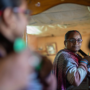 Deepa Bhatt, a member of the women's knitting circle, combs her hair in her home on the outskirts of Ranikhet, India on Dec. 4, 2018.