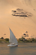 Felucca and sand dune on the Nile River.Aswan, Egypt.
