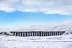 © Licensed to London News Pictures. 07/07/2016. Ingleton UK. File picture taken 14/01/2016 shows a train passing over Ribblehead Viaduct. After heavy rainfall in February caused a 500,000 ton land slip on the Settle to Carlisle railway which includes the world famous Ribblehead Viaduct the line has been partly closed, now a £23M repair project will see hundreds of concrete filled steel tubes set into the hillside to form a corridor on which a 100 metre long concrete slab will be placed to give the railway a solid base and the line will be fully re-opened next year. Photo credit: Andrew McCaren/LNP