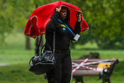 A key worker tries to protect themselves as they walk across the common - The first heavy rain doesn't stop, but greatly reduces, outdoor activity around Clapham Common. The 'lockdown' continues for the Coronavirus (Covid 19) outbreak in London.