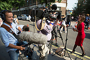 London, UK. Monday 22nd July 2013. Television news anchor shooting a piece to camera. Media frenzy outside St Mary's Hospital in London on the day that Kate Middleton Duchess of Cambridge was taken into hospital after going into labour. Immediately the global media village began to buzz with activity and the Royalist public started to arrive in numbers.