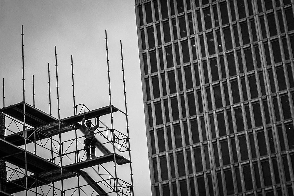Ställningsbyggare runt obelisken på Sergels Torg framför femte höghuset