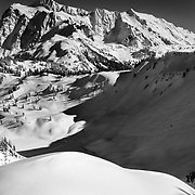 Mark Kogelmann drops into Mazama Bowl in late afternoon light with Mount Shuksan in the distance.