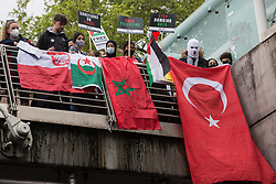 London, UK. 22nd May, 2021. Activists drape international flags on Hungerford bridge as tens of thousands of people take part in a National Demonstration for Palestine. It was organised by pro-Palestinian solidarity groups in protest against Israel's recent attacks on Gaza, its incursions at the Al-Aqsa mosque and its attempts to forcibly displace Palestinian families from the Sheikh Jarrah neighbourhood of East Jerusalem.