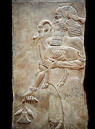 Stone relief sculptured panel of a man holding an Ibex and a poppy flower. Facade L. Inv AO 19872 from Dur Sharrukin the palace of Assyrian king Sargon II at Khorsabad, 713-706 BC.  Louvre Museum Room 4 , Paris .<br /> <br /> If you prefer to buy from our ALAMY PHOTO LIBRARY  Collection visit : https://www.alamy.com/portfolio/paul-williams-funkystock/ancient-assyria-antiquities.html  Refine search by adding background colour, place, subject, museum etc into the LOWER SEARCH WITHIN GALLERY box to <br /> <br /> Visit our ANCIENT ASSYRIAN PHOTO COLLECTIONS for more photos to download or buy as wall art prints https://funkystock.photoshelter.com/gallery-collection/Ancient-Assyrian-Art-Artefacts-Antiquities-Historic-Sites-Pictures-Images-of/C0000cjRqQyJjLag