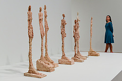 """© Licensed to London News Pictures. 08/05/2017. London, UK. A staff member views plaster works in the series """"Woman of Venice"""", 1956.  Preview of the UK's first major retrospective of Alberto Giacometti for 20 years at Tate Modern.  The exhibition runs 10 May to 10 September 2017. Photo credit : Stephen Chung/LNP"""