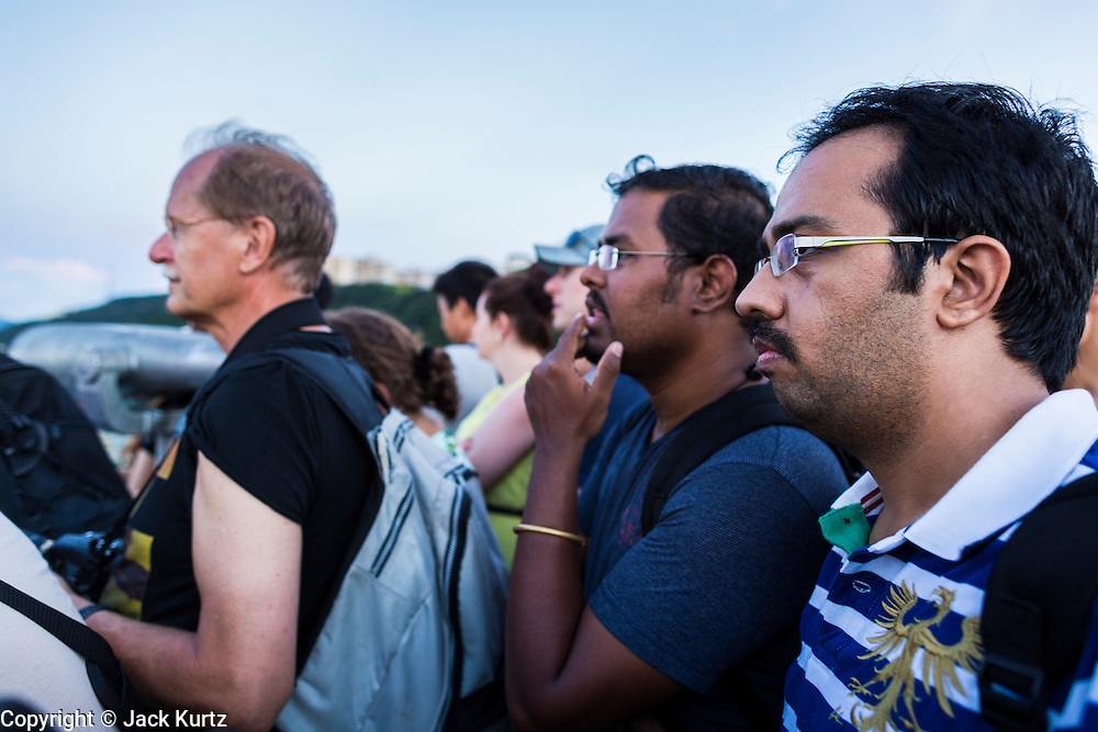 11 AUGUST 2013 - HONG KONG: Tourists at the top of Victoria Peak in Hong Kong watch the sunset. Hong Kong is one of the two Special Administrative Regions of the People's Republic of China, Macau is the other. It is situated on China's south coast and, enclosed by the Pearl River Delta and South China Sea, it is known for its skyline and deep natural harbour. Hong Kong is one of the most densely populated areas in the world, the  population is 93.6% ethnic Chinese and 6.4% from other groups. The Han Chinese majority originate mainly from the cities of Guangzhou and Taishan in the neighbouring Guangdong province.      PHOTO BY JACK KURTZ