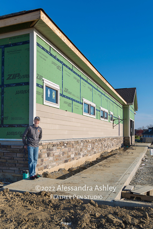Business owner at corner of new physical therapy and wellness center building, with siding and stone work in progress.