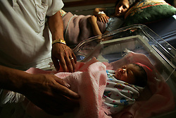 "Inas, the newborn daughter Ali Salah Tambre, 28 and Jawaher Ali Salah, 19, is comforted inside the Shepherd's Field Hospital in Bethlehem, Palestinian Territories, Nov. 15, 2004. The baby was born via cesarian section when she was breeched. Once the baby goes home and the family has gathered enough money, they will slaughter one sheep. When a boy is born, two sheep are killed in celebration. ""We are very poor, so all we can do right now is give sweets to our neighbors,"" said the father Ali. He used to work as a laborer in Israel but has been unemployed since the beginning of the Second Intifada."