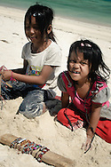 Indonesia, Lombok. Young girls selling simple handmade bracelets on Kuta Beach to earn some money and help their families.
