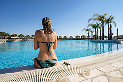 Rear view of mature woman sitting at poolside, Puglia, Italy