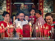 """07 FEBRUARY 2016 - BANGKOK, THAILAND: People light incense to make merit for Chinese New Year at a small Chinese shrine in Bangkok's Chinatown. Chinese New Year, also called Lunar New Year or Tet (in Vietnamese communities) starts Monday February 8. The coming year will be the """"Year of the Monkey."""" Thailand has the largest overseas Chinese population in the world; about 14 percent of Thais are of Chinese ancestry and some Chinese holidays, especially Chinese New Year, are widely celebrated in Thailand.        PHOTO BY JACK KURTZ"""