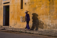 An old woman walks along the street in the late afternoon on Hoi An's waterfront.