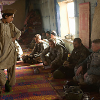 A young boy looks on as Afghan elders and US Forces sit down to a mini Shura at the onset of Operation Winterstand, a Humanitarian Assitance mission, part of the COIN (counter insurgency) program being actioned in Rebat, Pakitika Province, Afghanistan on the 19th of January 2008