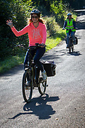 A woman waves and smiles as she cycles on an electric bike followed by another woman on a country lane in Staplehurst, Kent, England, UK.