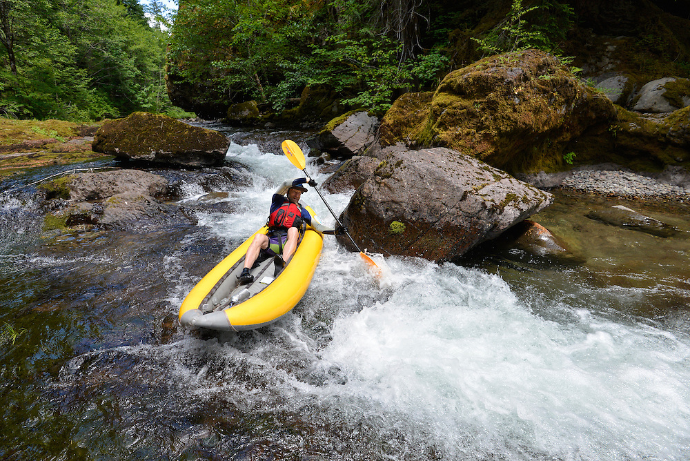 Paddling an inflatable kayak down the Blue River in the Cascade Range of Oregon.
