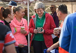 © Licensed to London News Pictures. 19/04/2019. Maidenhead, UK. Prime Minister THERESA MAY drinks tea with locals before helping out as a marshal at the Maidenhead Easter 10 run in her constituency of Maidenhead in Berkshire. Parliament currently on Easter recess after an extension to Article 50 was granted by the EU. Photo credit: Ben Cawthra/LNP