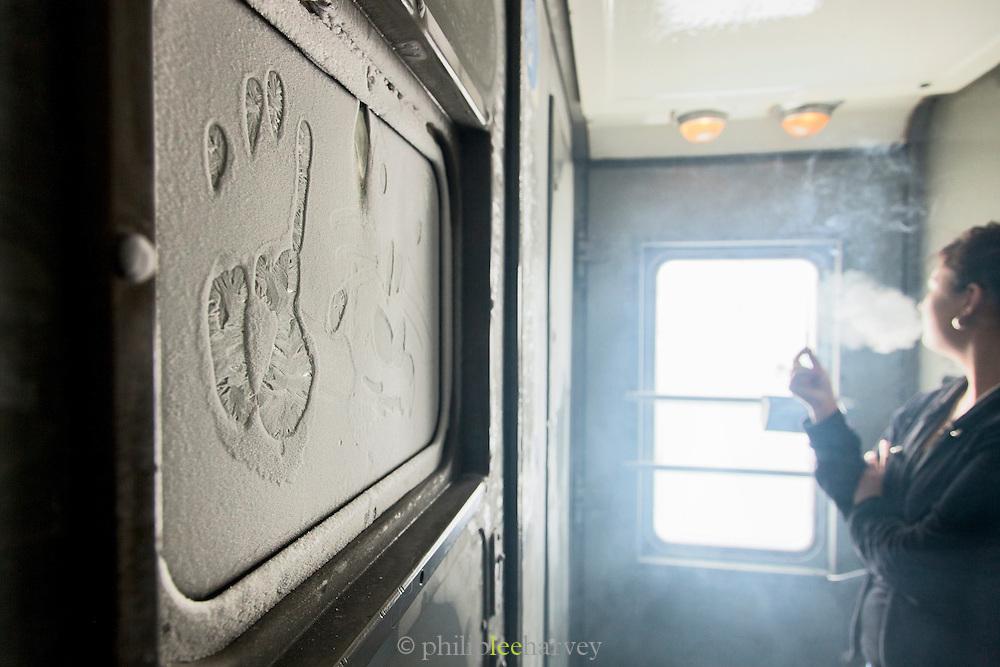 Frozen windowpane in the smoking area on-board the BAM Railway line. Baikal-Amur Mainline). Siberia, Russia