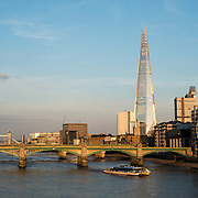 A view of the London skyline looking east from Millenium Bridge. The bridge in the foreground is the Southwark Bridge, with the Tower Bridge in the distance at left. The tall angular building is known as The Shard.