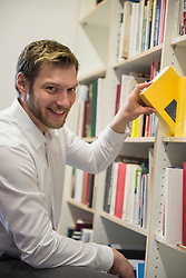 Portrait of a mid adult businessman choosing books from bookshelf in an office, Bavaria, Germany