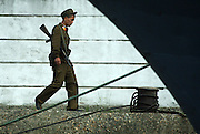 """A North Korean soldier guards the port of Sinuiju July 8, 2006. China and North Korea are separated by the Yalu River, upon which Chinese tourists take pleaure cruises across the water to  observe their less economically developed neighbors.  North Korea has threatened to take """"stronger physical actions"""" after Japan imposed punitive measures in response to its barrage of missile tests and pushed for international sanctions. North Korea has vowed to carry out more launches and has said it will use force if the international community tries to stop it. DPRK, north korea, china, dandong, border, liaoning, democratic, people's, rebiblic, of, korea, nuclear, test, rice, japan, arms, race, weapons, stalinist, communist, kin jong il"""