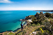 Man out walking on the cliff paths and enjoying the views across the coastliine and towards Vicard Harbour, a quiet calm bay surrounding by turquoise water in Jersey, CI