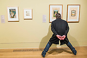 A man crouches to get a better view in the Trophies of empire room - Artist and Empire - a new Tate Britain exhibition about Imperial visual culture, examining the people who helped to create or confront the British Empire in their art. It features over 200 paintings, drawings, photographs, sculptures and artefacts from across the British Isles, North America, the Caribbean, the Pacific, Asia and Africa. Exhibition highlights include: Major historic paintings by the likes of Johan Zoffany, George Stubbs, Lady Butler Anthony Van Dyck and Thomas Daniell; Rare Maori portraits which are being exhibited in London for the first time in almost 100 years; The first chance to photograph one of the nation's favourite paintings, The North-West Passage 1874 by John Everett Millais since undergoing new conservation; and new work by artist Andrew Gilbert, made especially for the exhibition. Artist and Empire at Tate Britain from 25 November 2015 to 10 April 2016.